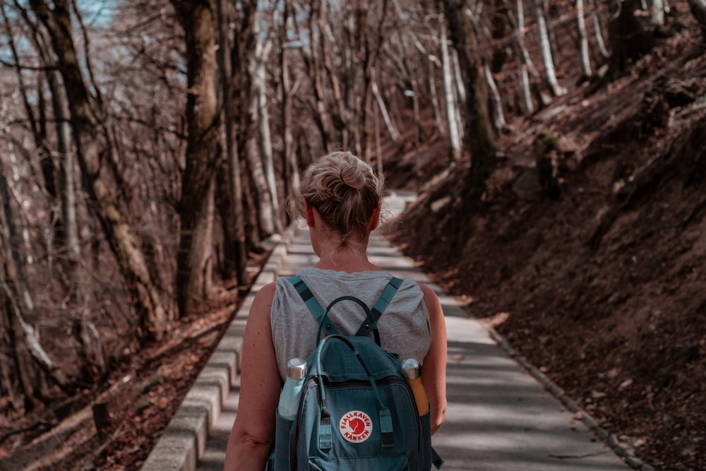 woman in blue backpack walking on pathway between trees during daytime