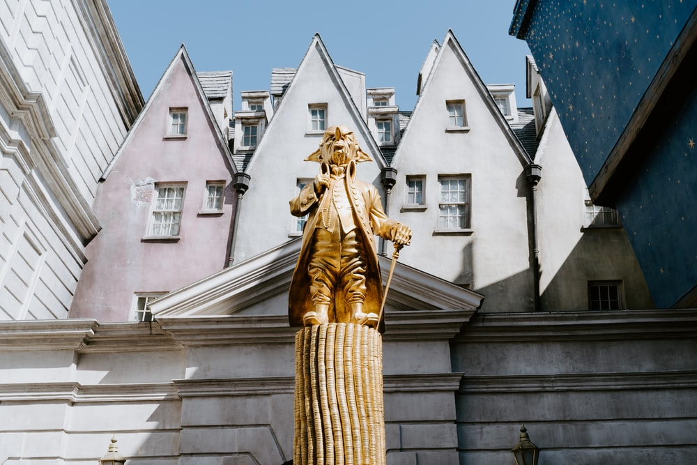 gold statue near white concrete building during daytime