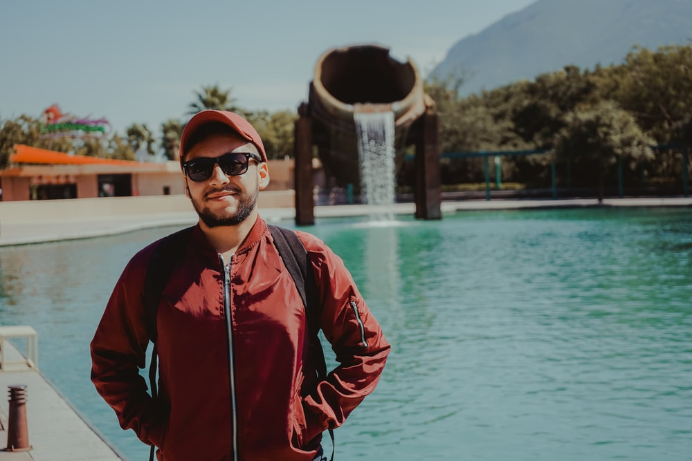 man in red zip up jacket standing near body of water during daytime
