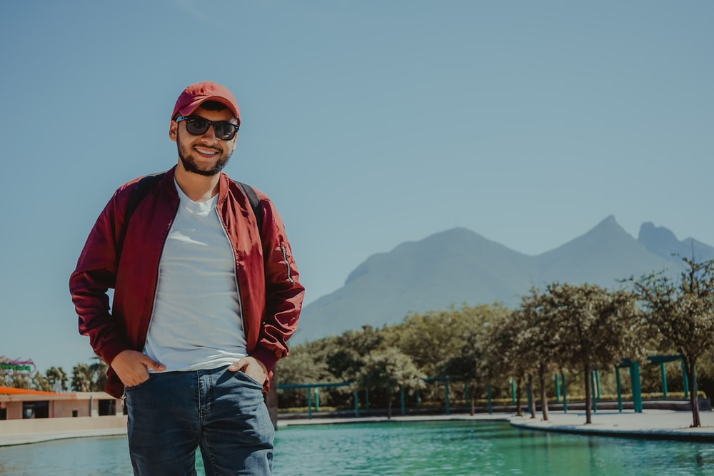man in red jacket standing near body of water during daytime