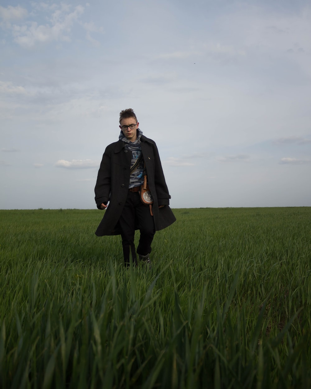 woman in black coat standing on green grass field under gray cloudy sky during daytime