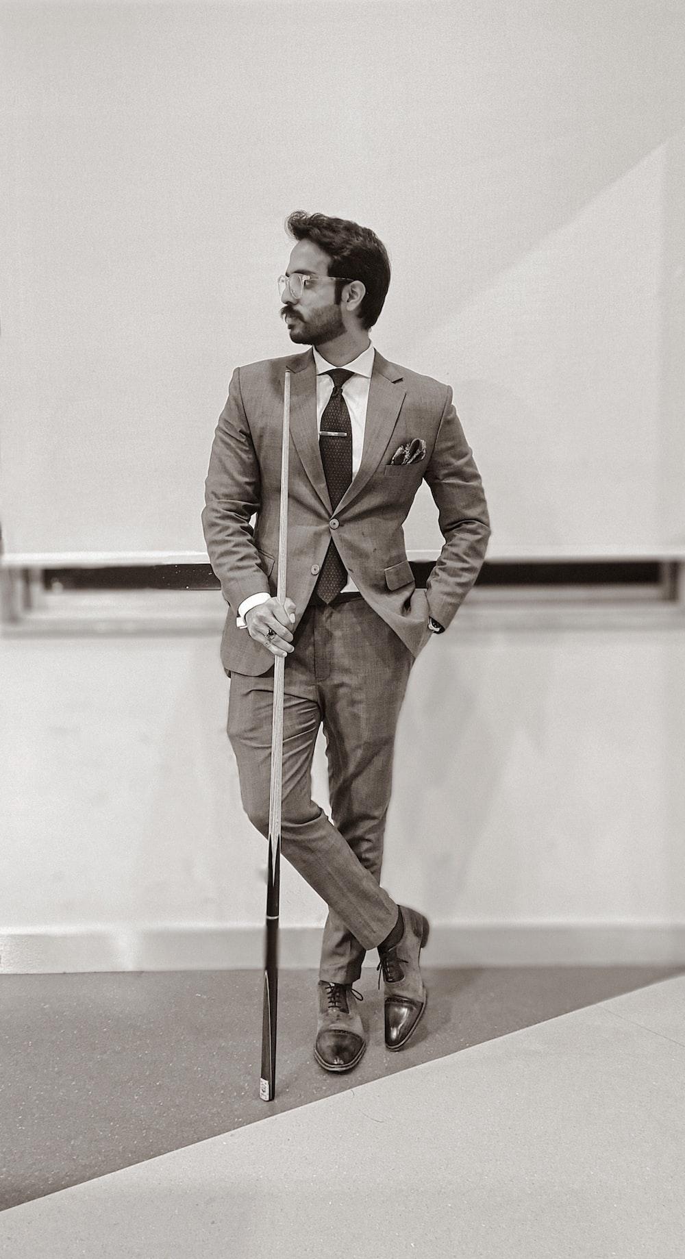 man in brown suit holding walking stick