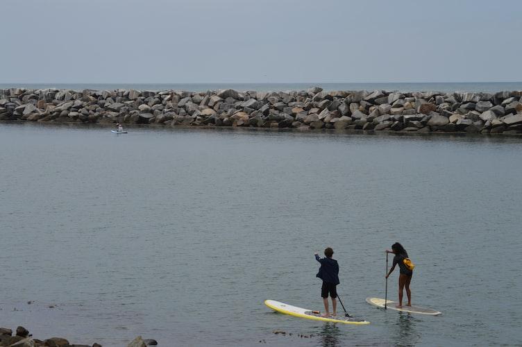 sustainable travel - paddleboarding guy and girl
