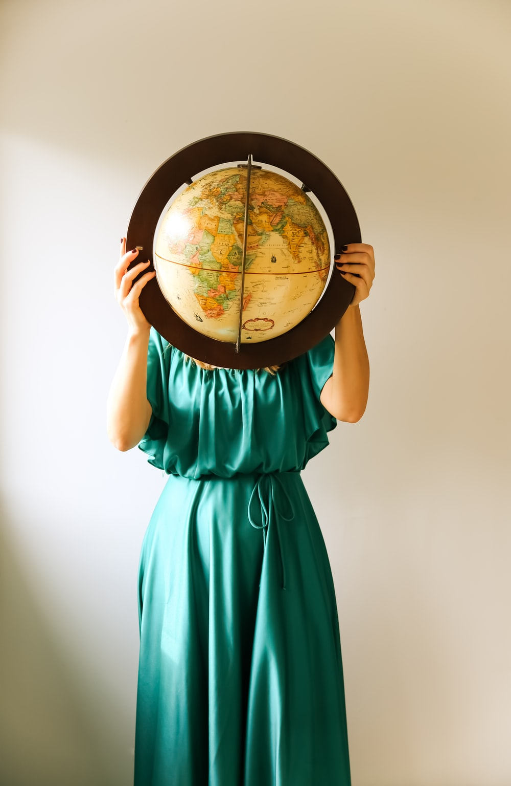 woman in teal dress holding round mirror