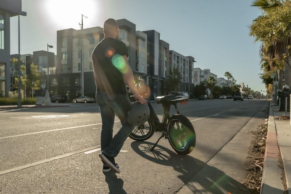 man in black jacket and black pants riding on black bicycle during daytime