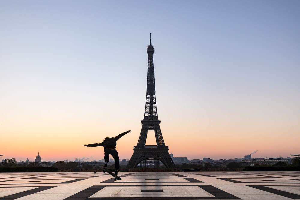 silhouette of man jumping on gray concrete pathway near eiffel tower during sunset