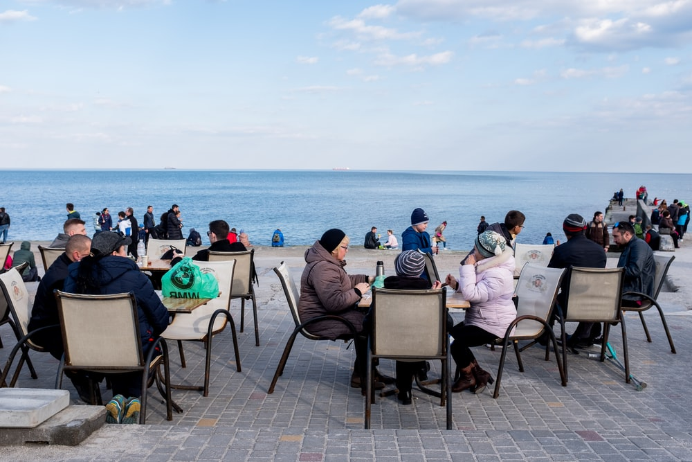 people sitting on chair near sea during daytime