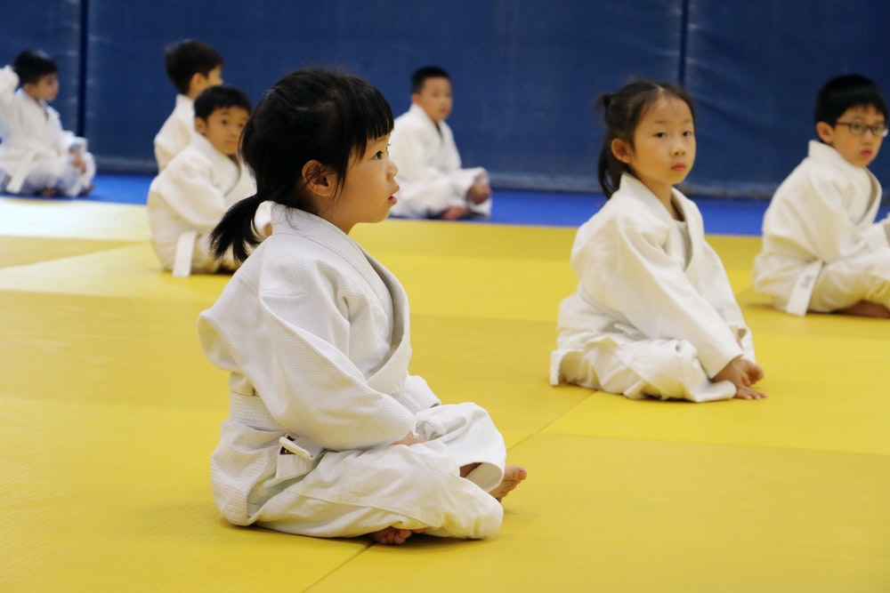 2 children in white robe sitting on yellow floor