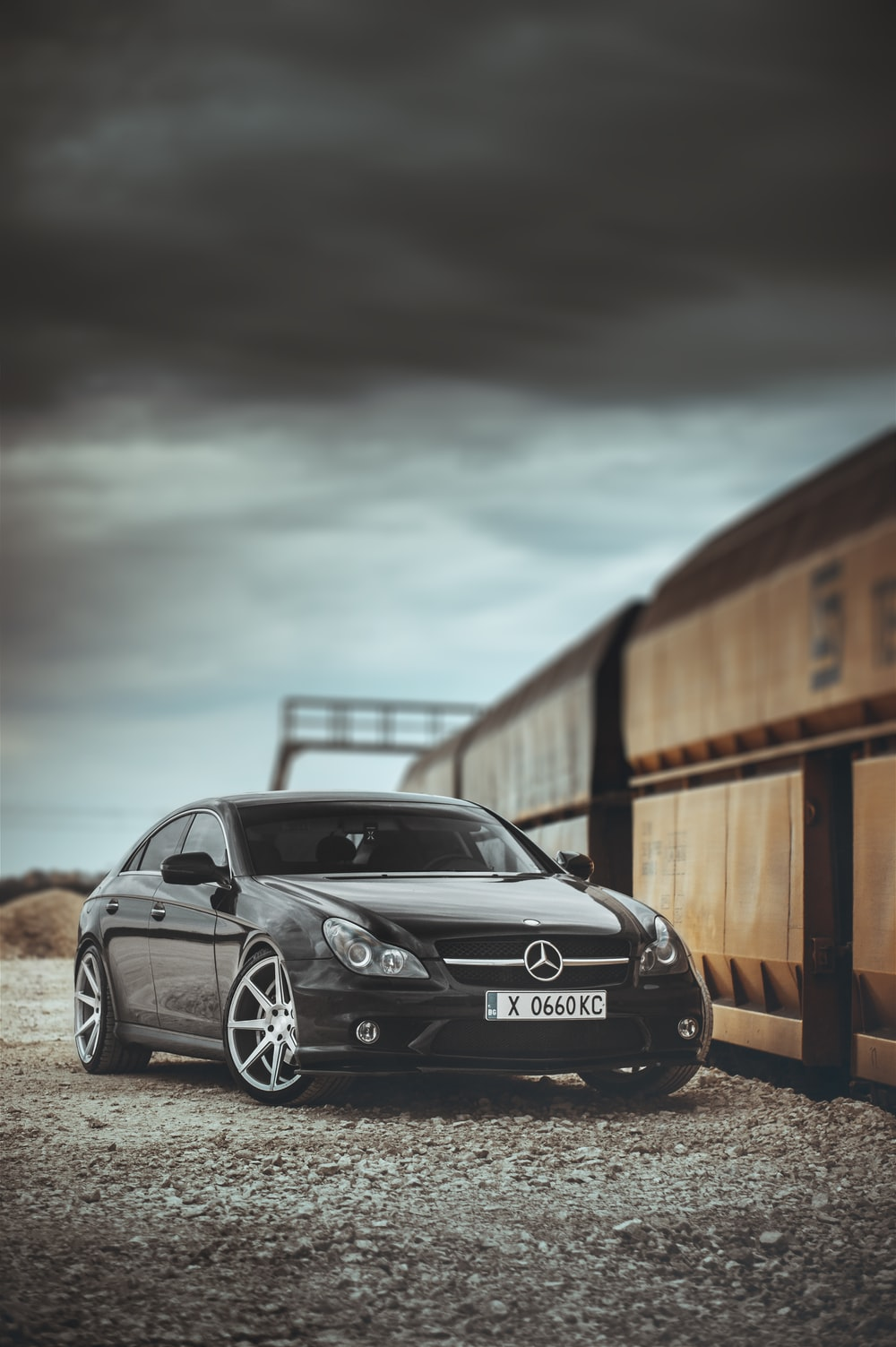 black mercedes benz coupe parked beside brown wooden fence during daytime