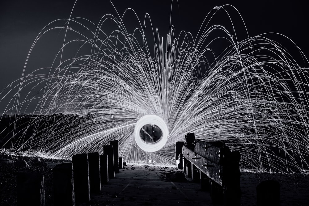 steel wool photography of a man standing on a bridge