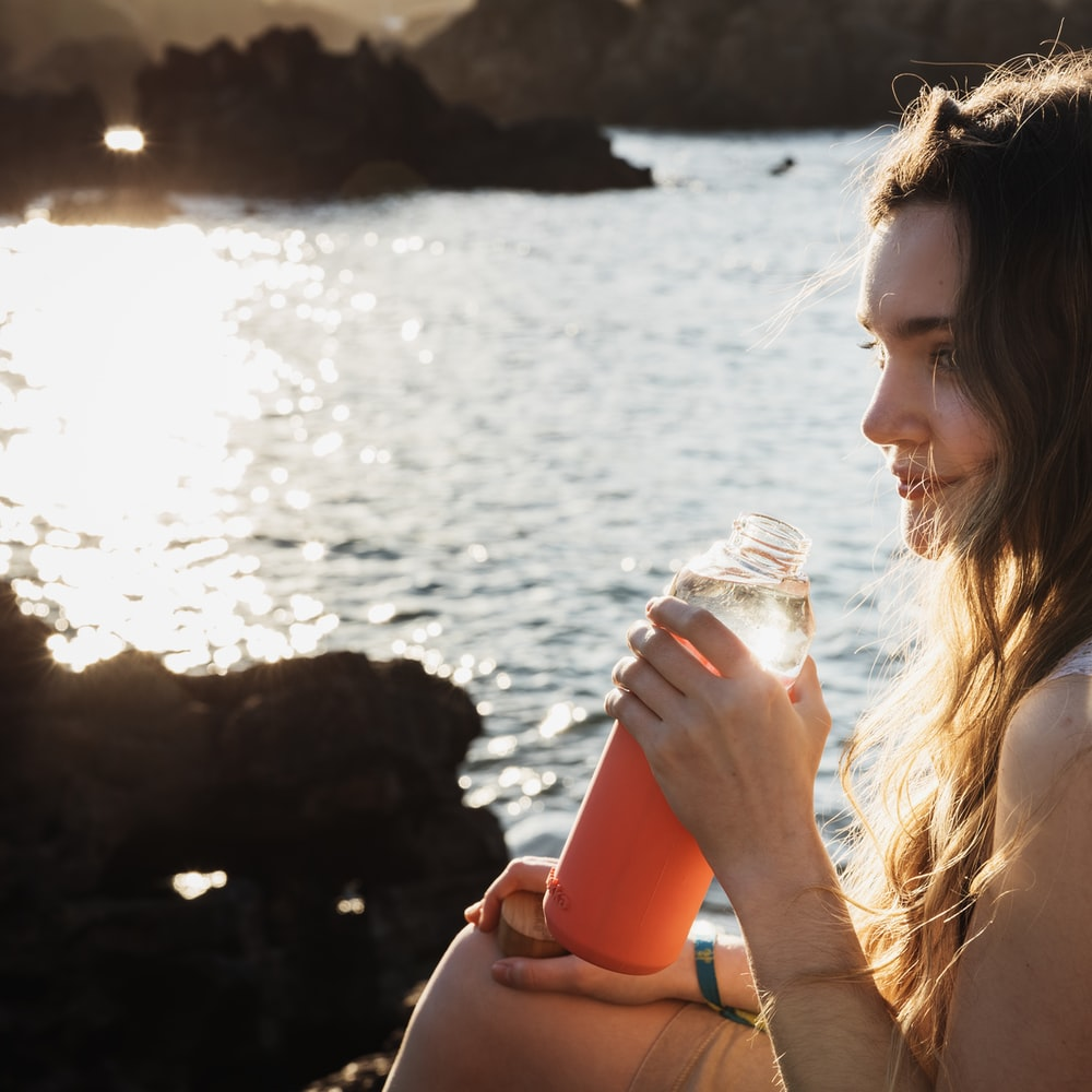 woman drinking water from clear plastic bottle