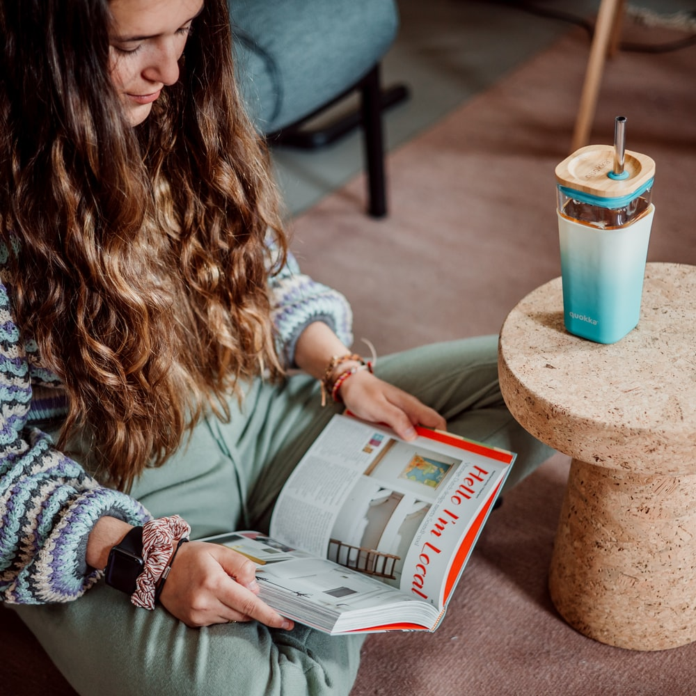woman in white sweater reading newspaper