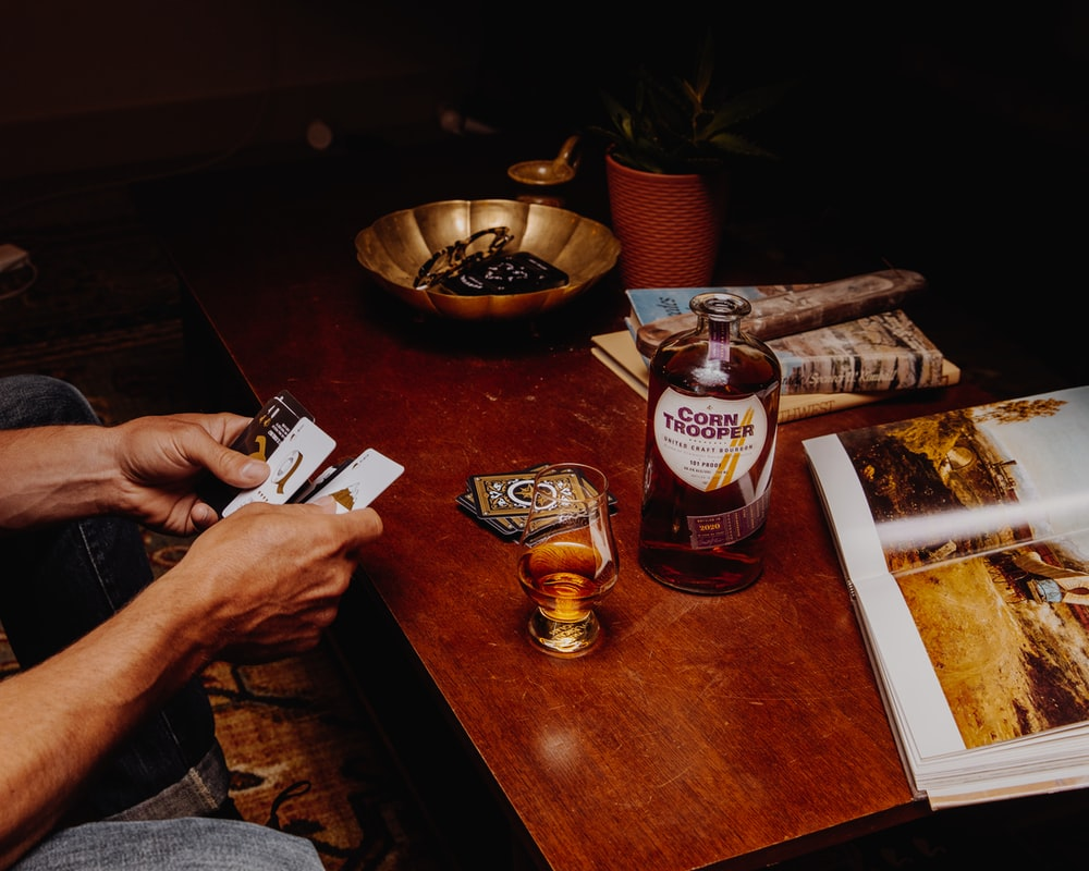 person holding a playing cards on brown wooden table