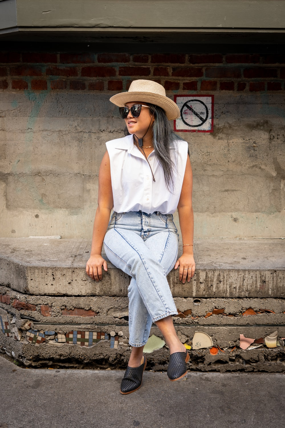 woman in white sleeveless shirt and blue denim jeans sitting on concrete stairs