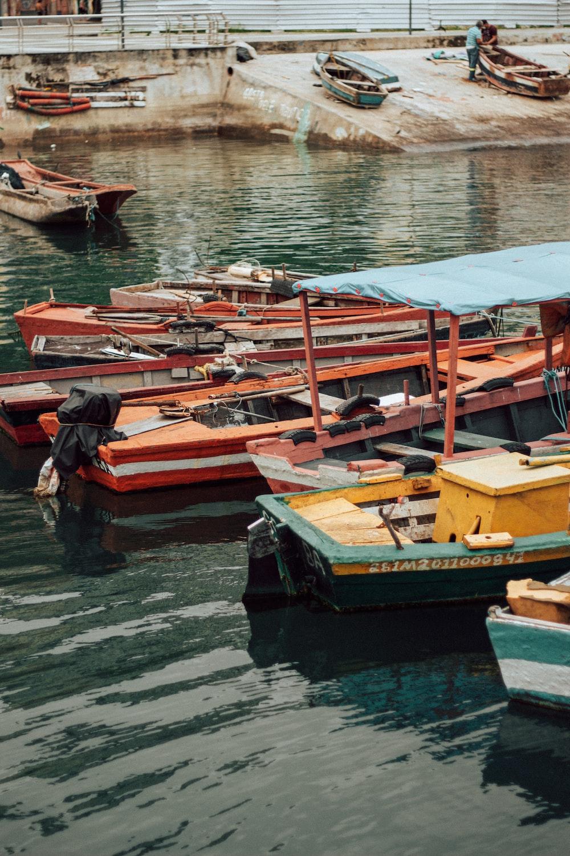 man in black jacket sitting on brown wooden boat dock during daytime