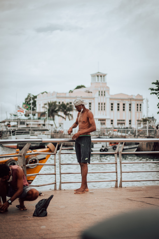 man in black shorts walking on brown wooden dock during daytime