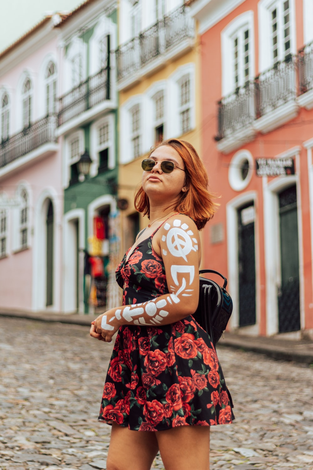 woman in black and red floral dress wearing black sunglasses standing on street during daytime