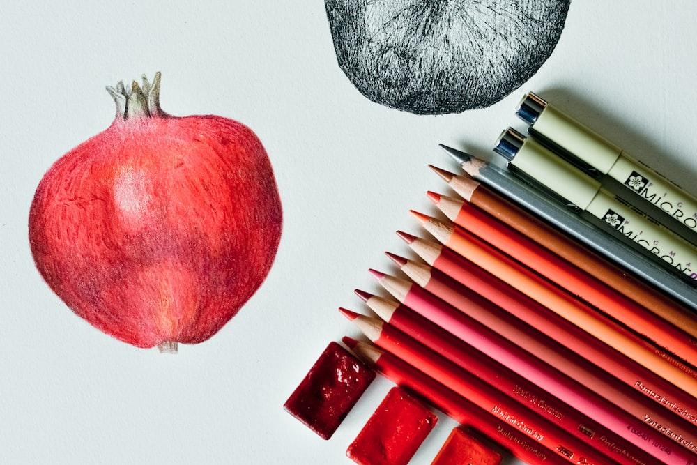 red apple fruit beside black and white pen