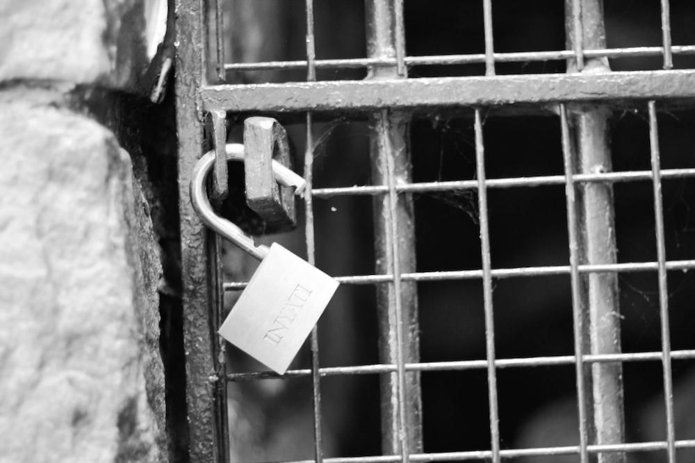 padlock on metal gate during daytime