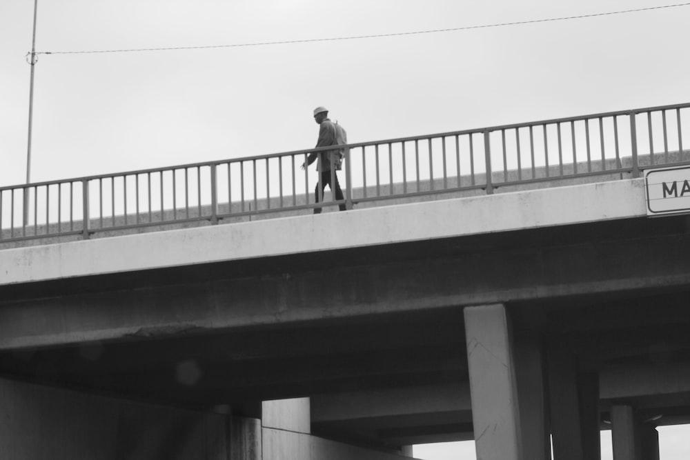 man in black jacket and pants standing on bridge