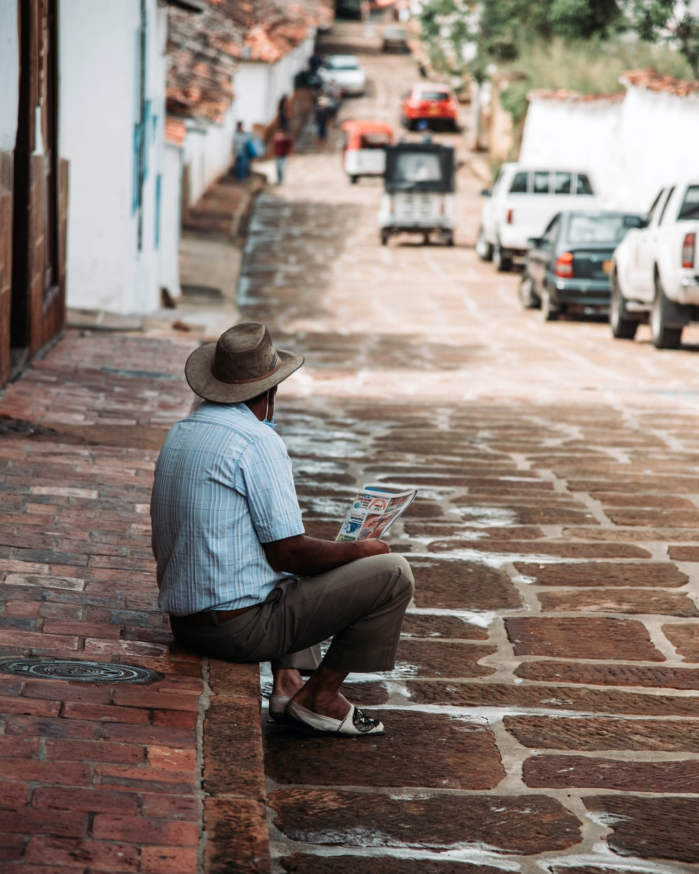man in blue dress shirt sitting on red concrete bench