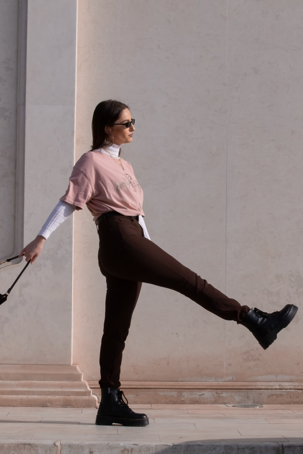 woman in pink shirt and black pants holding walking stick