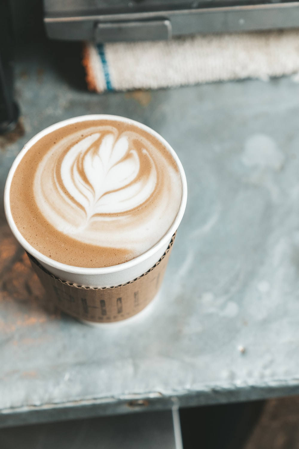 white and brown coffee cup
