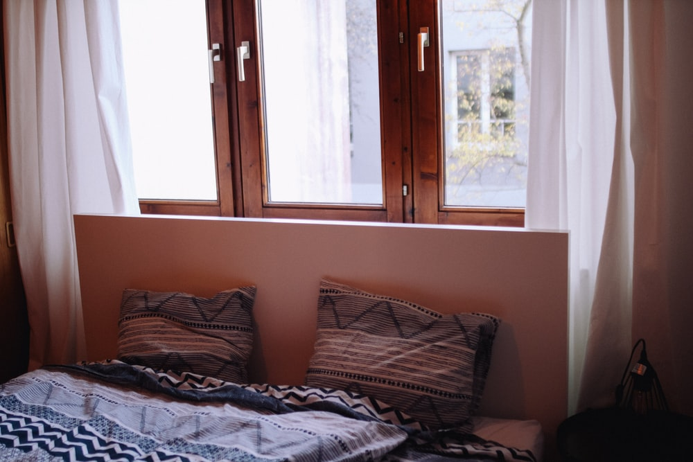 brown wooden bed frame with gray and white bed linen