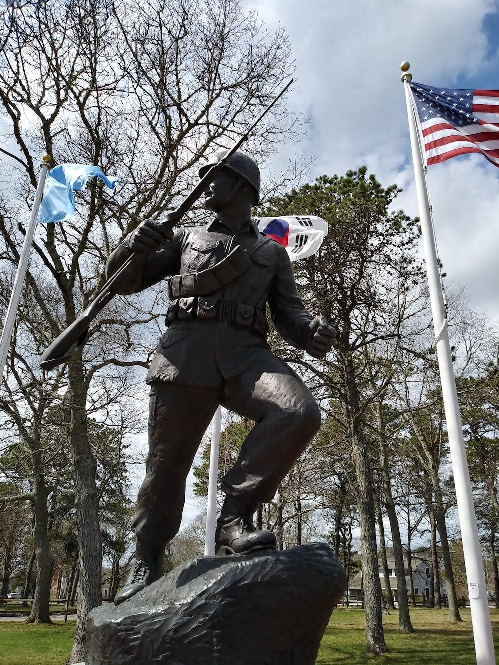 man in black helmet and black jacket holding flag of us a during daytime