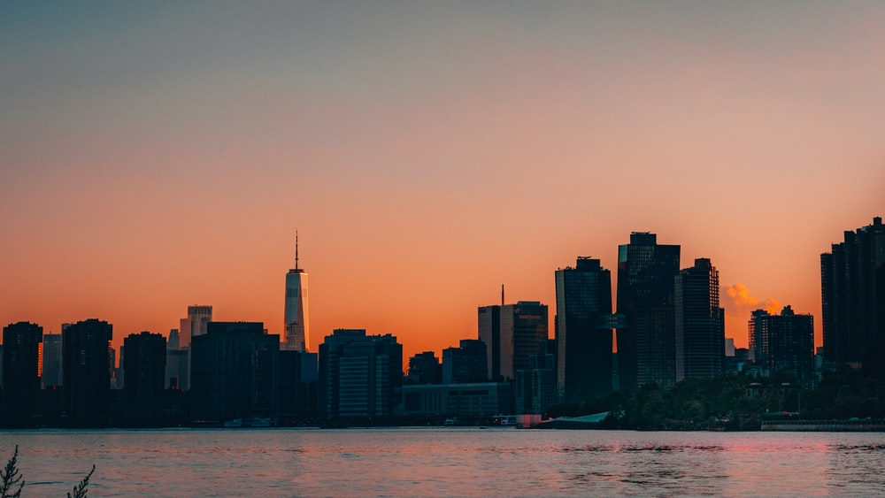 city skyline during sunset with body of water