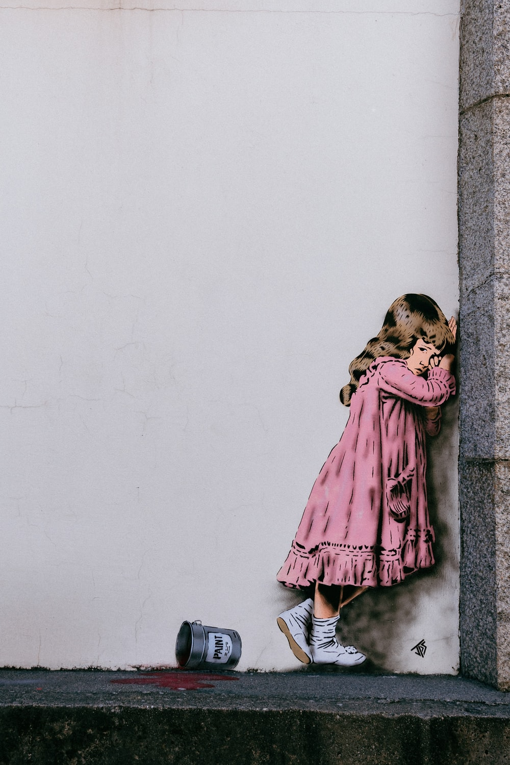 girl in pink dress leaning on wall