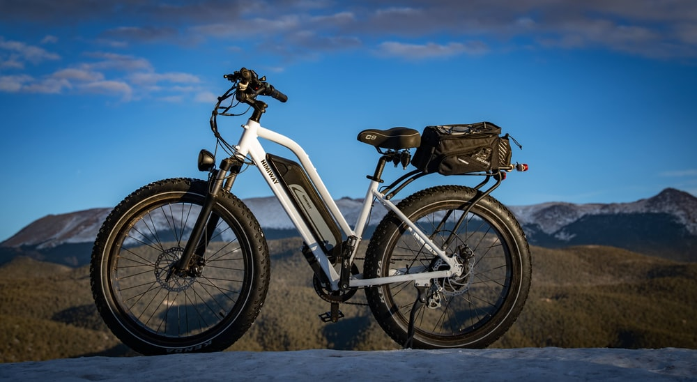 white and black mountain bike on brown field during daytime
