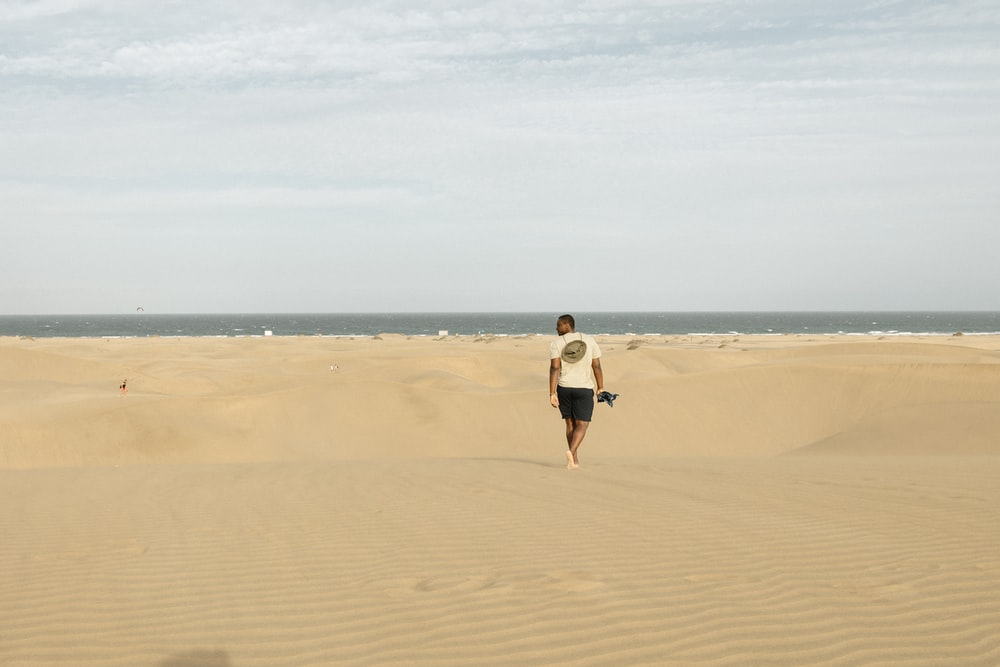 woman in white shirt and black shorts walking on brown sand during daytime