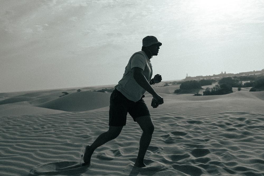 man in white shirt and black shorts walking on beach during daytime