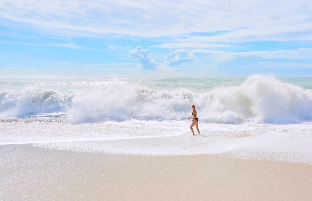 person in black shorts walking on seashore during daytime