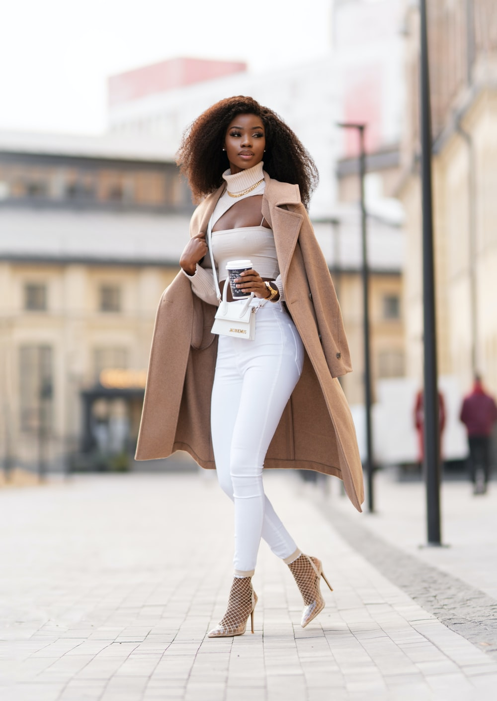 woman in white long sleeve shirt and white pants standing on road during daytime