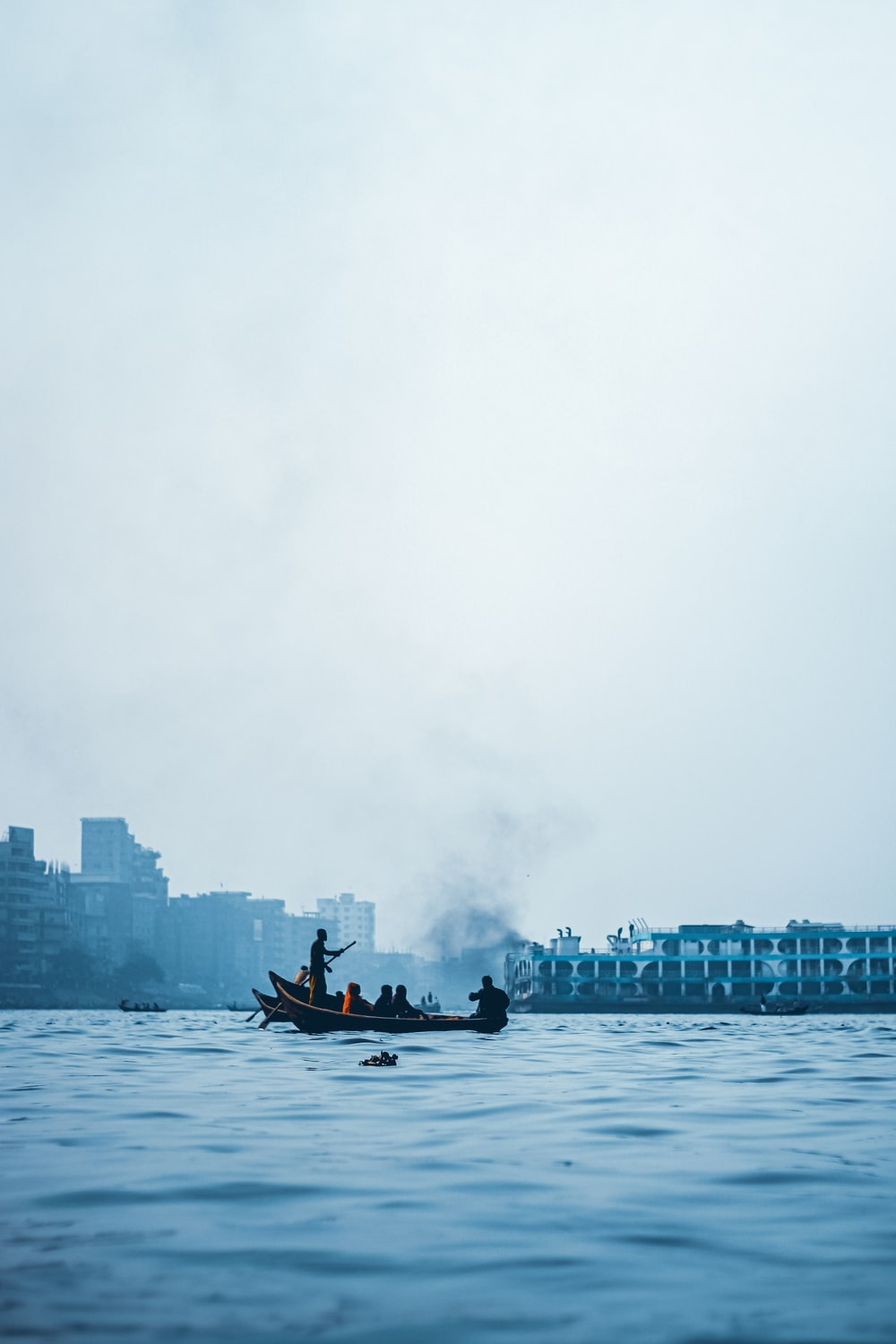 man riding on boat on water near city buildings during daytime