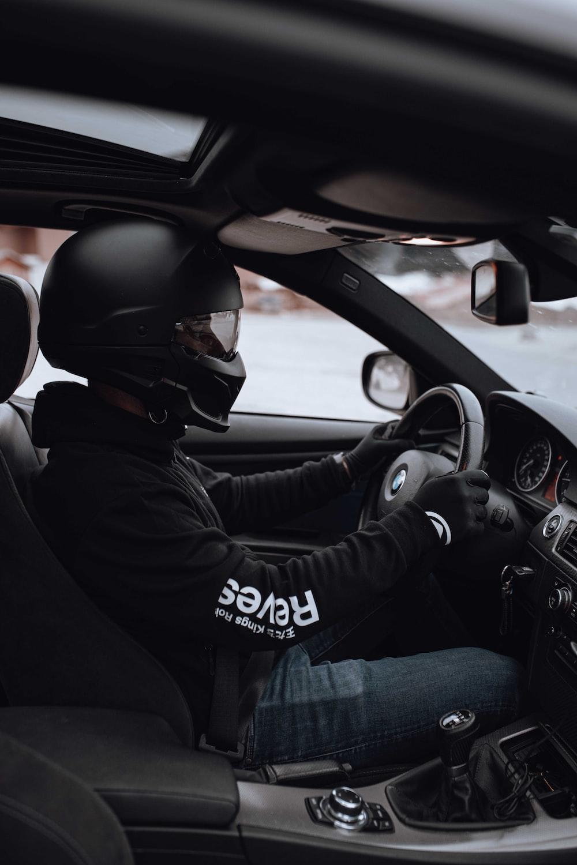 man in black jacket driving car