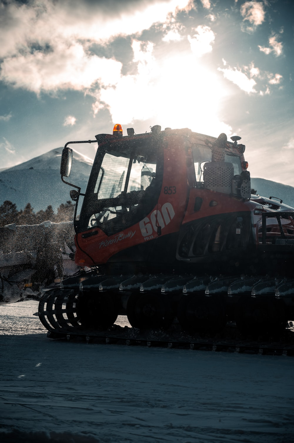 orange and black heavy equipment on snow covered ground during daytime