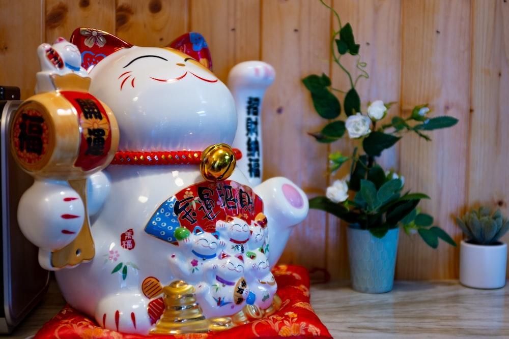 red and white ceramic cat figurine