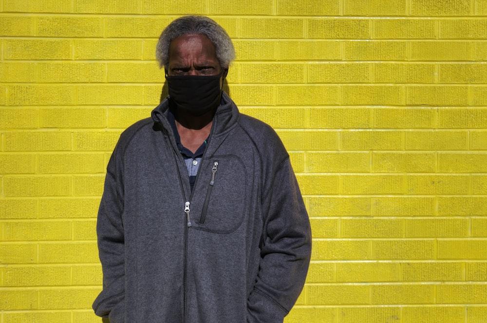 man in black zip up jacket standing beside yellow brick wall