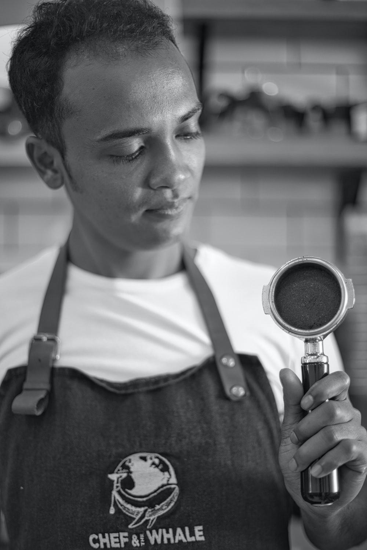 man in black vest holding magnifying glass