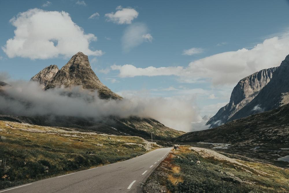 gray asphalt road near mountain under blue sky during daytime