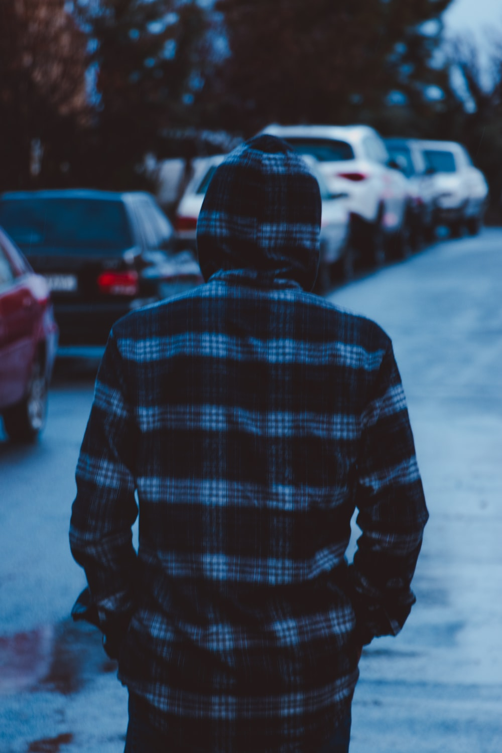 person in blue and white plaid hoodie standing on street during daytime