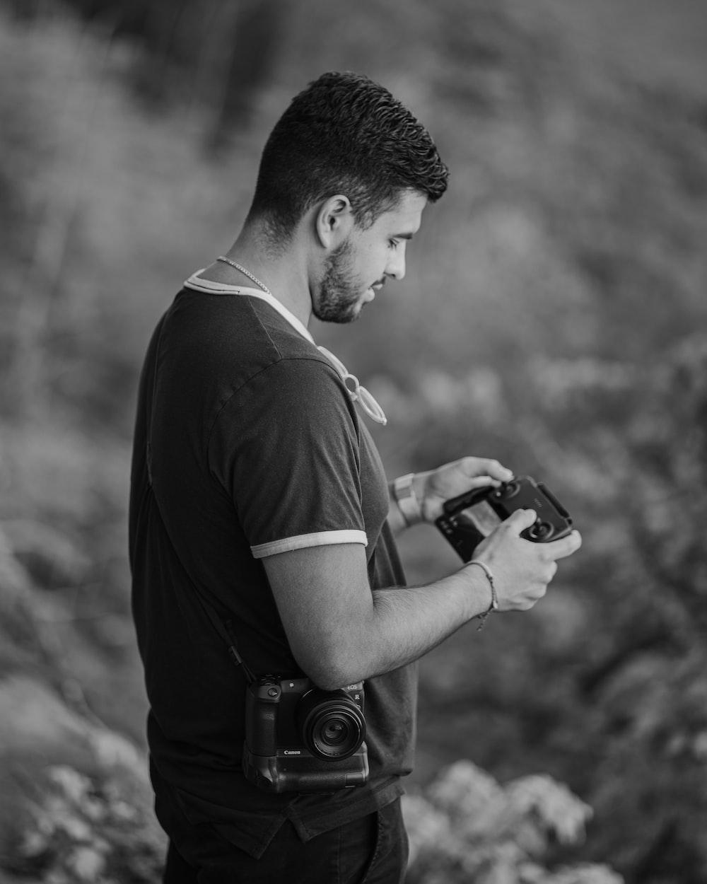 man in black t-shirt holding camera