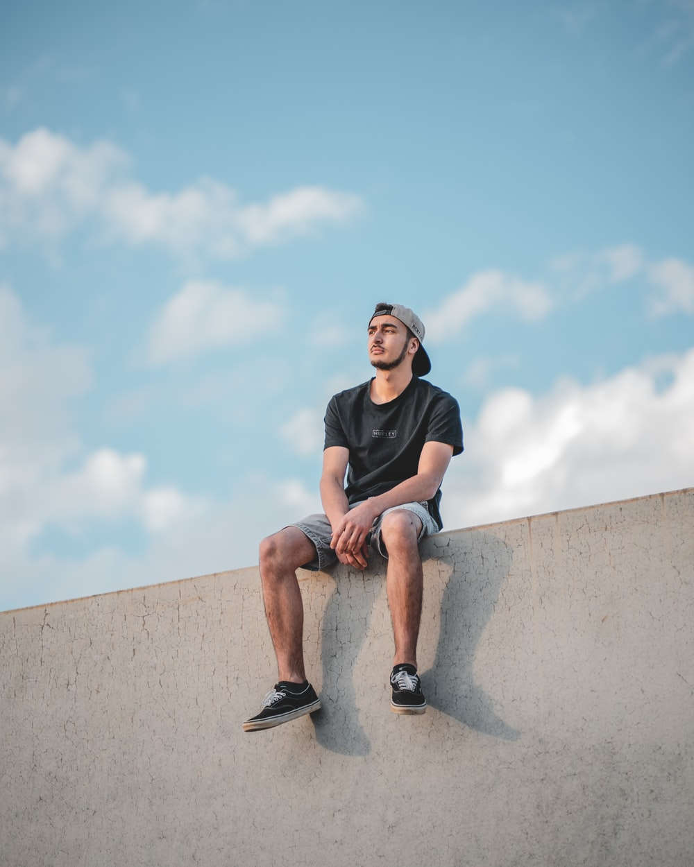 man in black crew neck t-shirt sitting on gray concrete wall under blue sky during