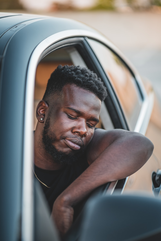 man in white tank top sitting inside car