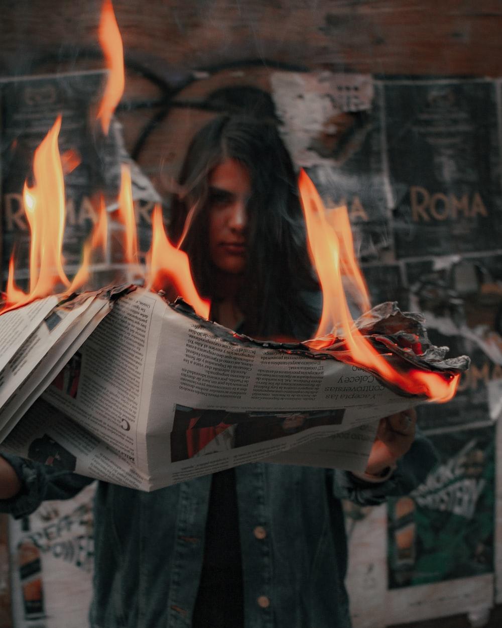 woman in black jacket holding newspaper