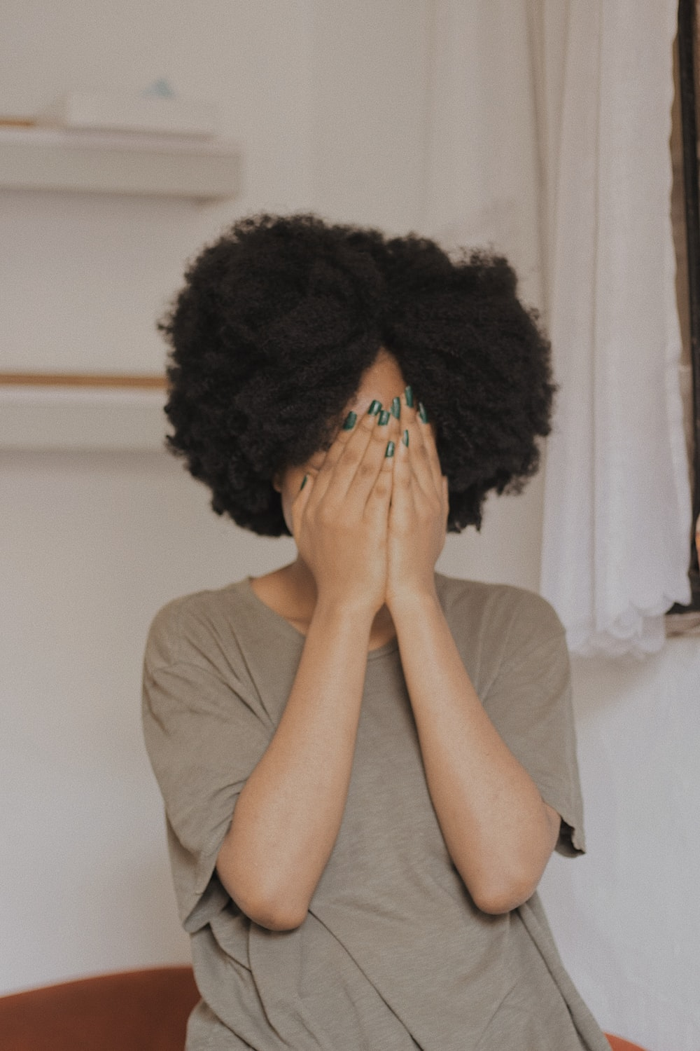 woman in gray t-shirt covering face with both hands
