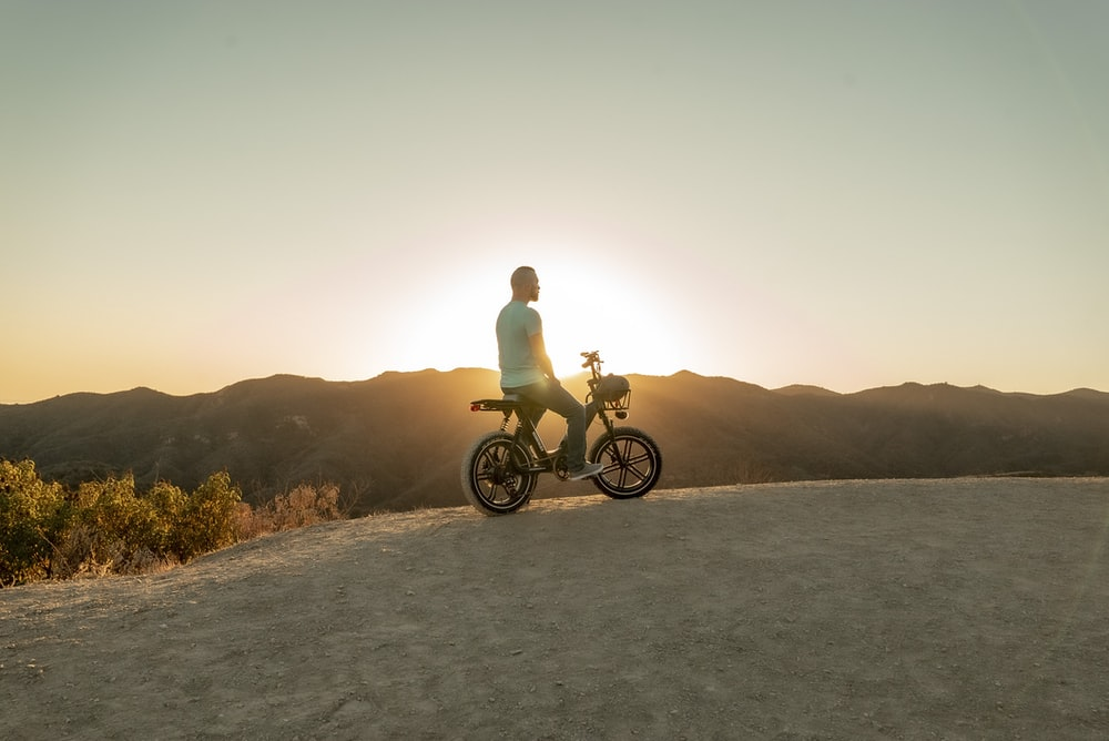 man riding motorcycle on gray sand during sunset